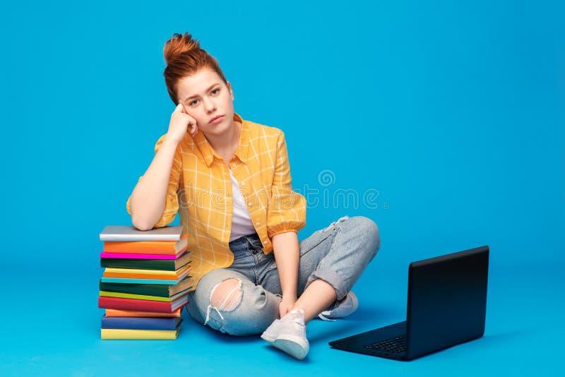 Ledsen röd haired tonårs- studentflicka med bärbara datorn royaltyfria bilder
