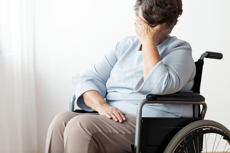 Ledsen rörelsehindrad hög kvinna i ett wheelchar arkivfoton