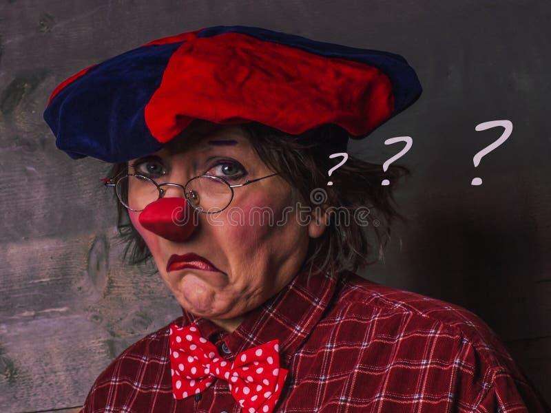 Ledsen, rubbningclown med en röd näsa och tre frågefläckar i högt royaltyfri bild