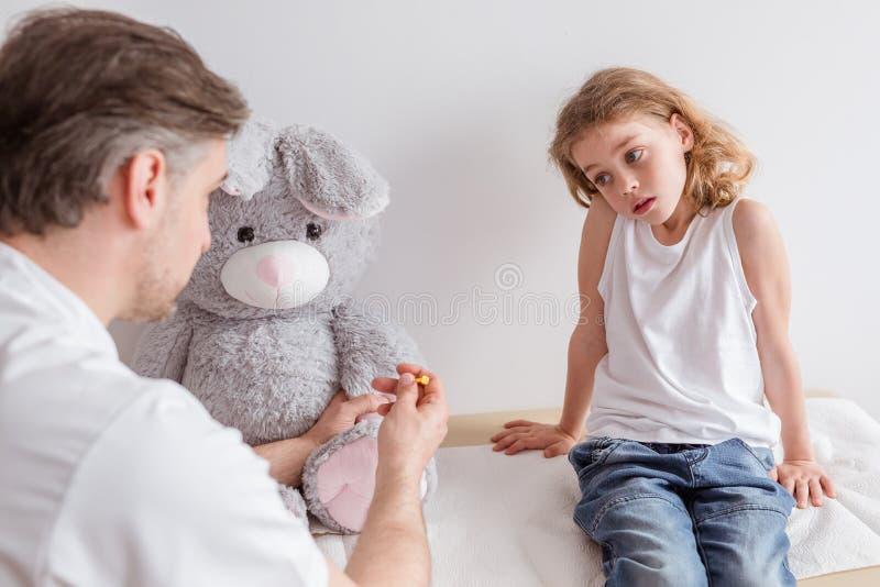 Ledsen sjukt barn och pediatriskt i doktorns kontor arkivfoton