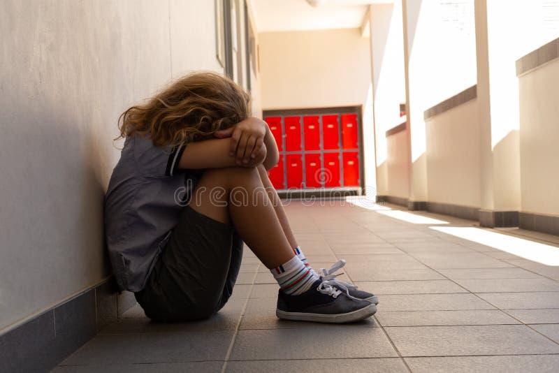 Ledsen skolflicka som sitter på golvet med hans huvud ner arkivbild