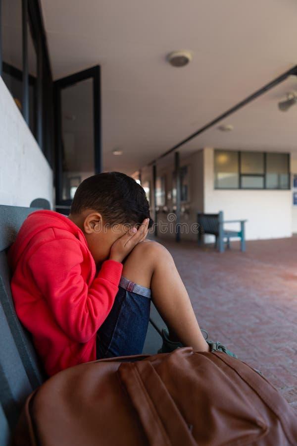 Ledsen skolpojke som bara sitter med händer som täcker hans framsida på bänk i korridor arkivbilder