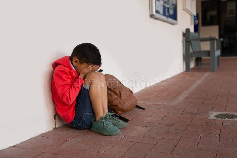 Ledsen skolpojke som bara sitter med händer som täcker hans framsida på golv i korridor arkivbilder
