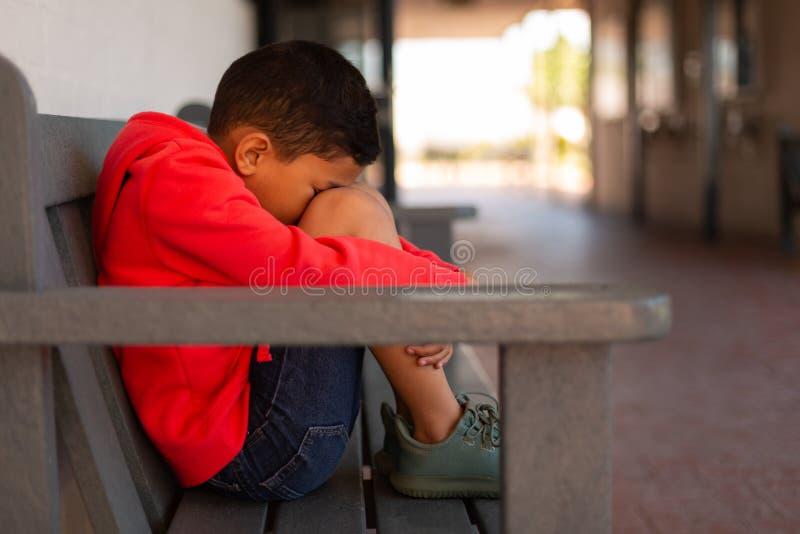 Ledsen skolpojke som bara sitter på bänk i korridor arkivbilder