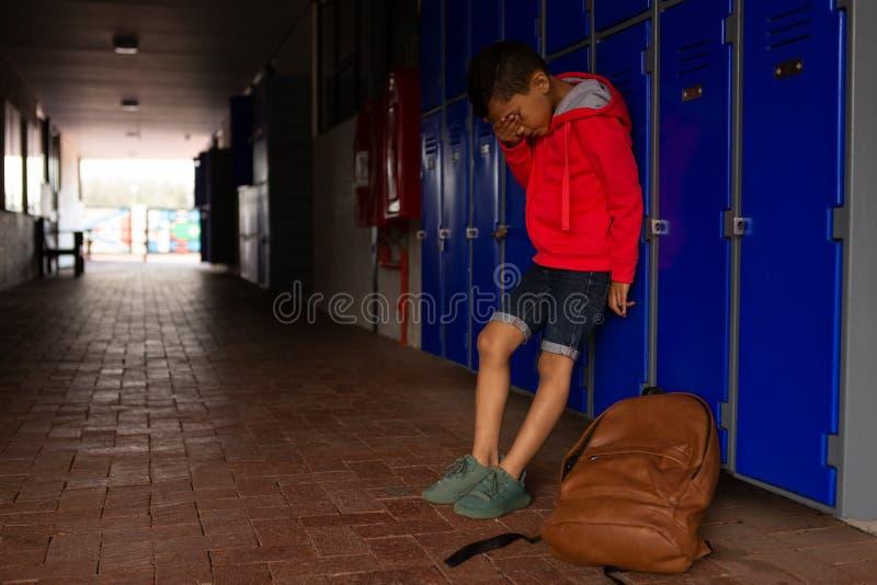 Ledsen skolpojke som bara står i korridor fotografering för bildbyråer