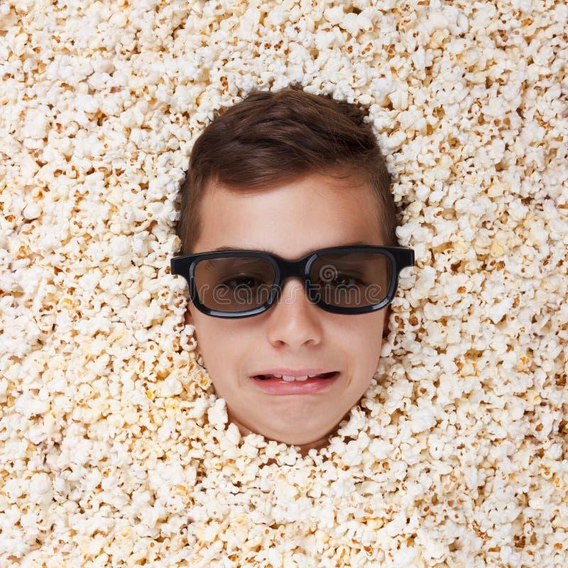 Ledsen skriande ung pojke i stereo- exponeringsglas som ser ut ur popcorn royaltyfria bilder