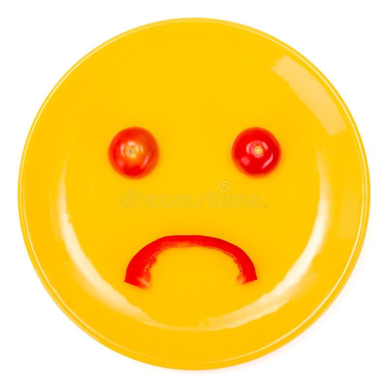 Ledsen smileyframsida som göras på plattan arkivbild