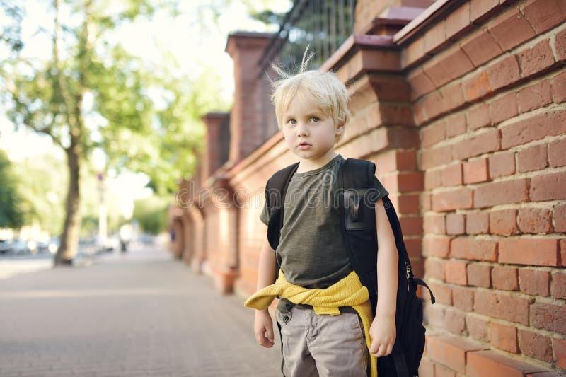 Ledsen stressad pys med ryggsäcken Barnmotvillighet som går att skola Förtvivlan och fördjupning som trakasserar, våld, förföljel fotografering för bildbyråer