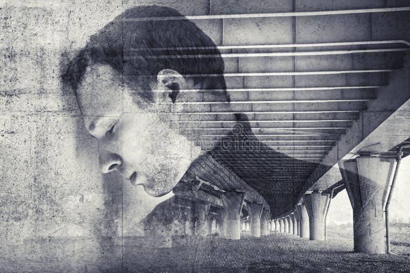 Ledsen stressad ung man med betongväggbakgrund fotografering för bildbyråer