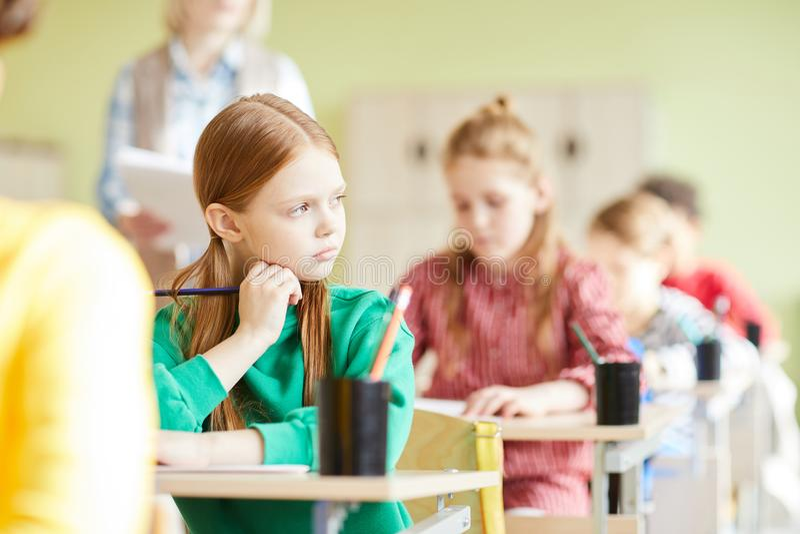 Ledsen studentflicka i klassrum royaltyfri foto