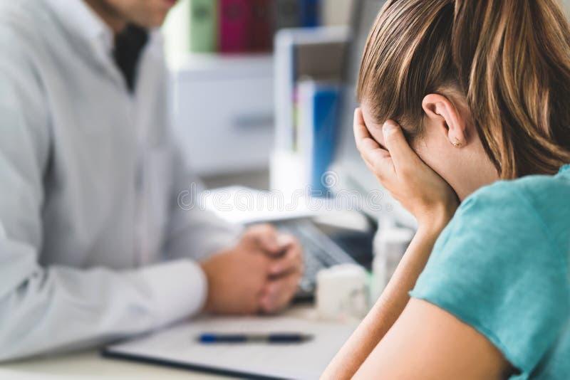 Ledsen tålmodig besöka doktor Ung kvinna med spänningen eller sammanbrott som får hjälp från medicinsk professionell eller terape arkivbild