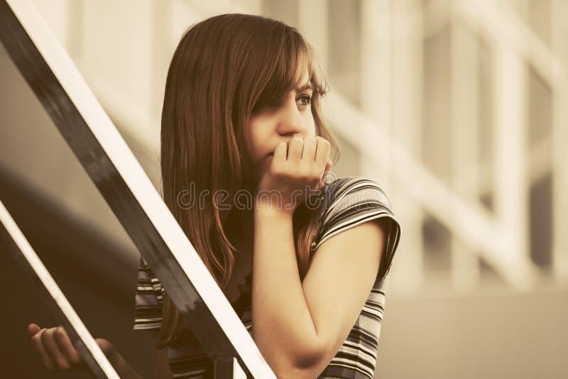 Ledsen tonårig flicka på moment mot en skolabyggnad arkivfoto