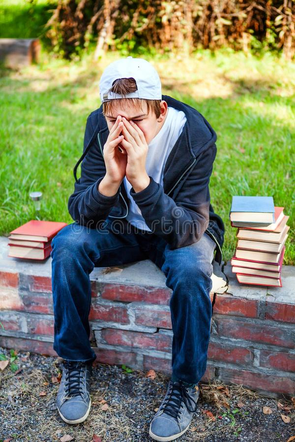 Ledsen tonåring med böcker arkivbilder