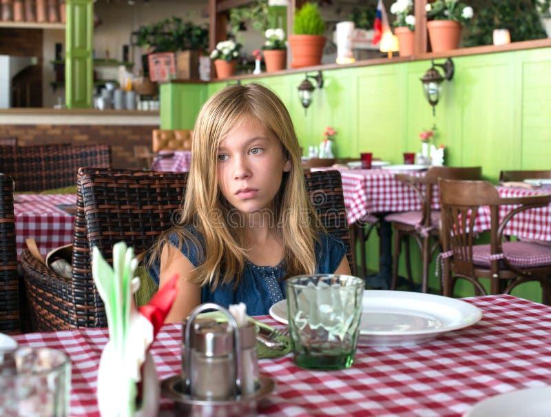 Ledsen tonåringflicka i en restaurang Ensam flicka som väntar i en caffee royaltyfria foton