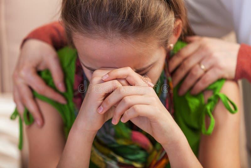 Ledsen tonårs- flicka som propping hennes huvud i förtvivlan - kvinnahänder som rymmer och tröstar henne royaltyfria foton