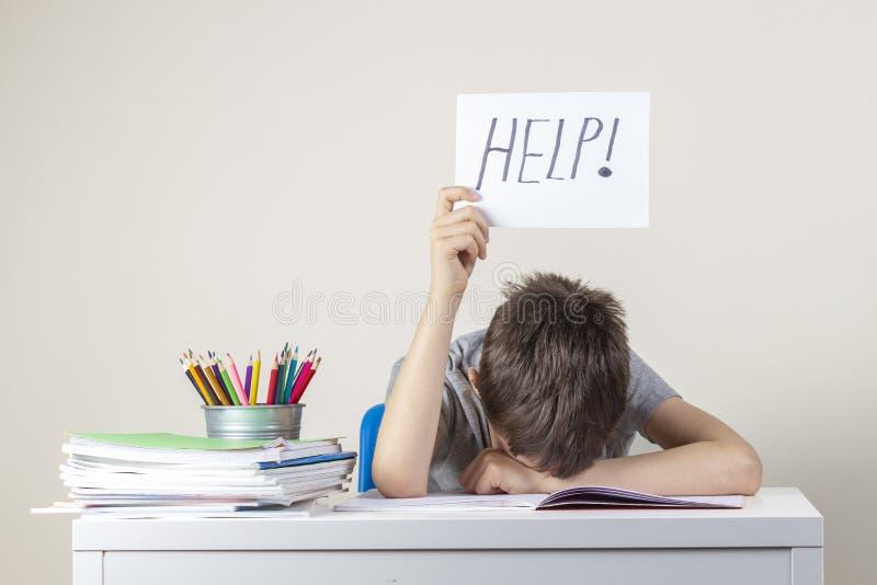 Ledsen trött frustrerad pojke som sitter på tabellen med många böcker och rymmer papper med ordhjälp L royaltyfri foto