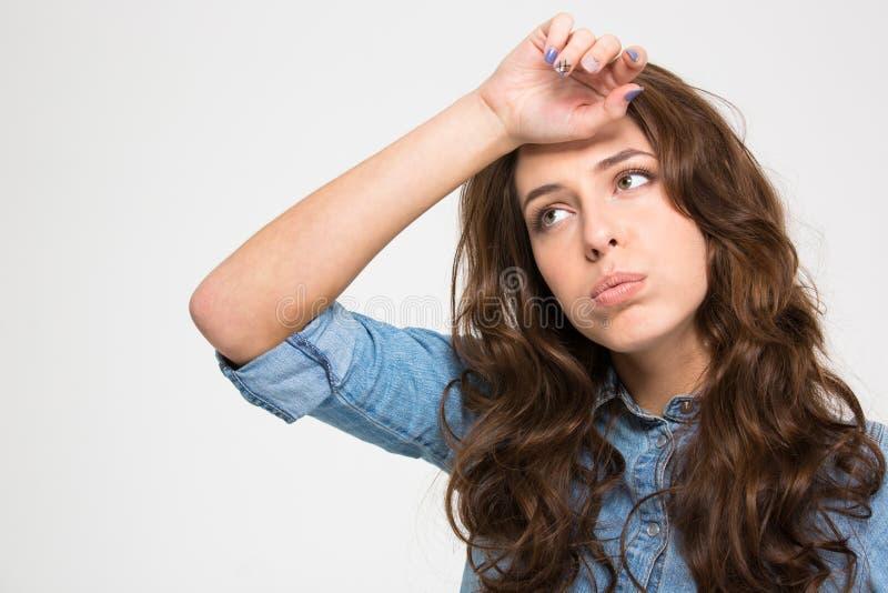 Ledsen trött ung kvinna med handen på pannan arkivfoto