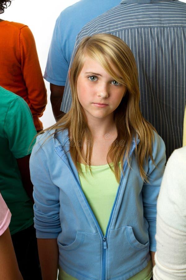Ledsen ung flicka som bara känner sig i en folkmassa fotografering för bildbyråer