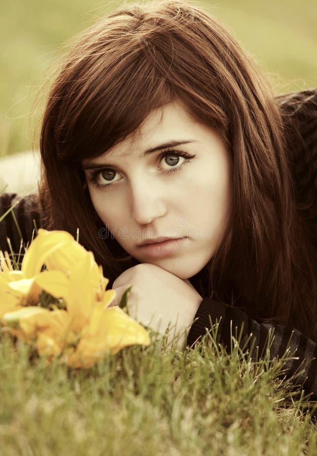 Ledsen ung kvinna med blommor som ligger på gräset royaltyfri fotografi