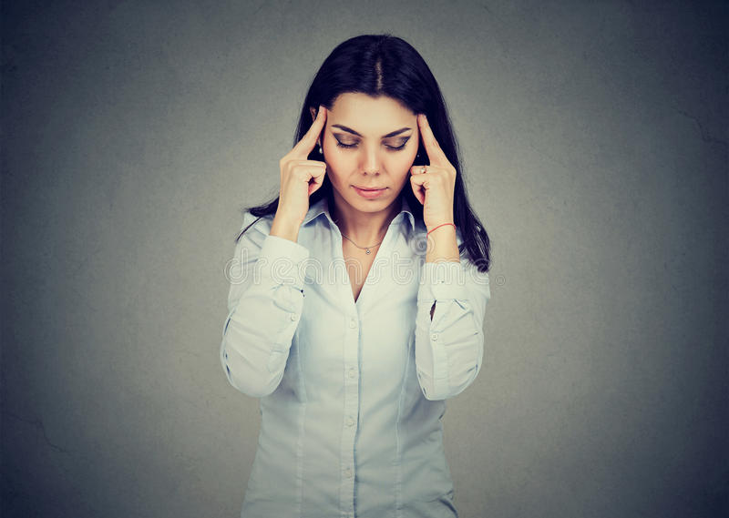 Ledsen ung kvinna med det bekymrade stressade framsidauttryckt som har huvudvärk royaltyfri bild