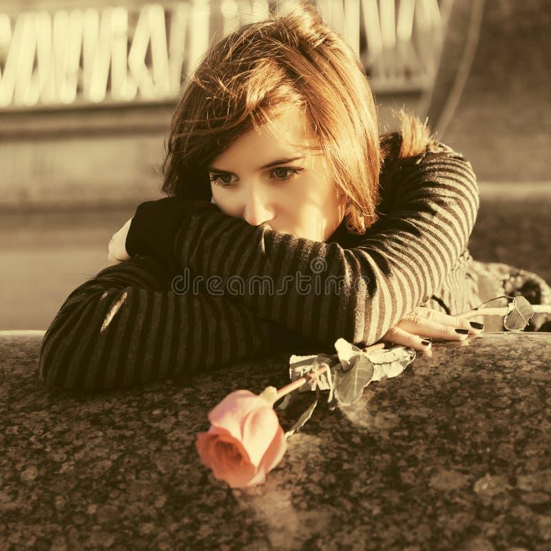 Ledsen ung kvinna med en röd ros royaltyfri fotografi