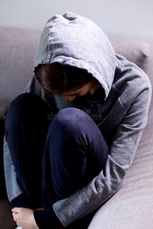 Ledsen ung kvinna med huven som tänker känsligt borttappat sammanträde på soffamedelskott royaltyfri foto