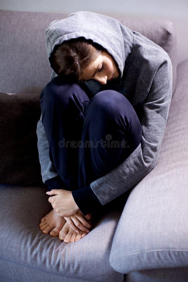 Ledsen ung kvinna med huven som tänker känsligt borttappat sammanträde på soffasned bollskott royaltyfri fotografi