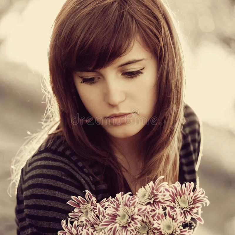 Ledsen ung kvinna med utomhus- blommor royaltyfri foto