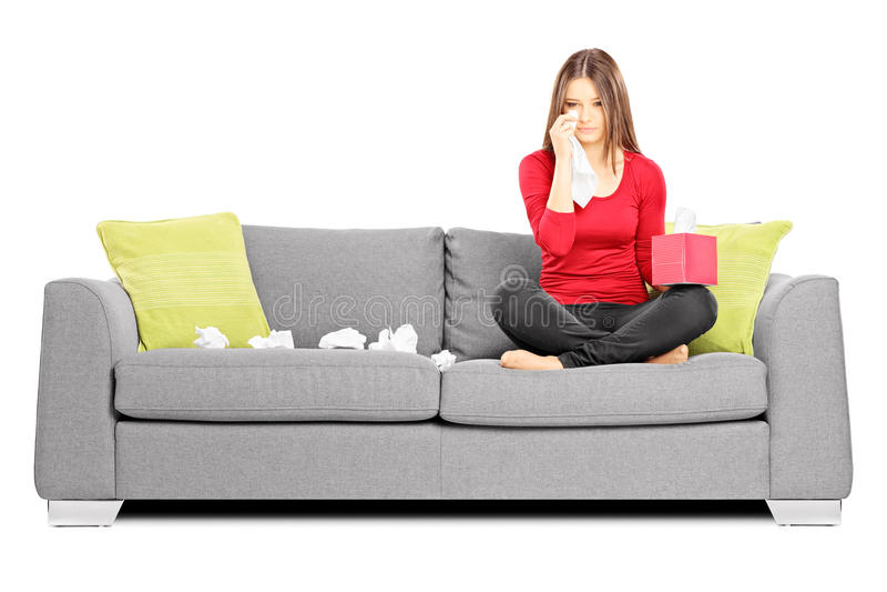 Ledsen ung kvinna på en soffa som torkar henne ögon från gråt arkivbild