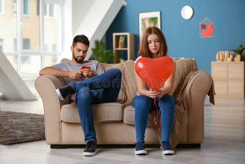 Ledsen ung kvinna som rymmer denformade ballongen nära den likgiltiga mannen som hemma spelar med mobiltelefonen Barnpar som gr?l arkivbilder