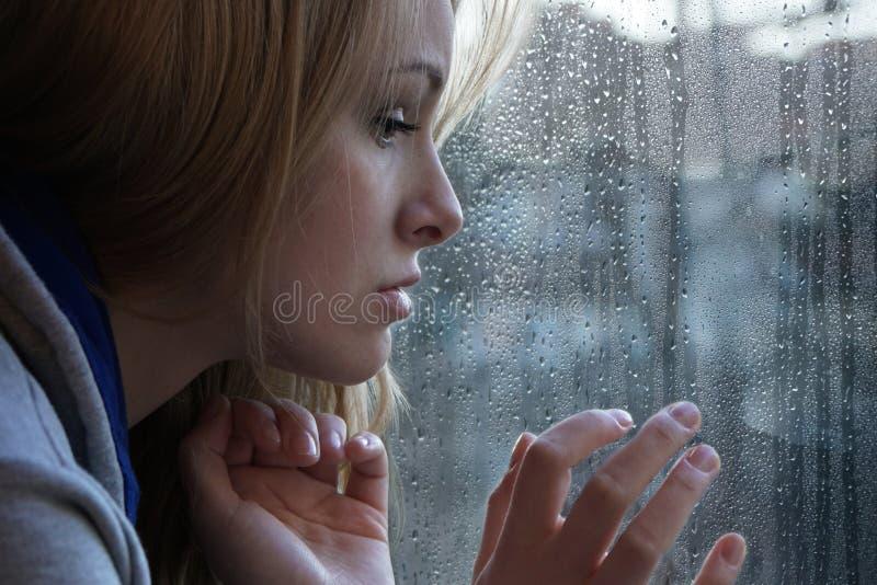 Ledsen ung kvinna som ser till och med fönster på regnig dag arkivbilder