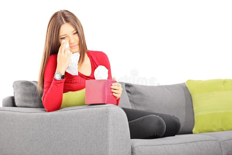 Ledsen ung kvinnlig på en soffa som torkar henne ögon från gråt arkivfoton