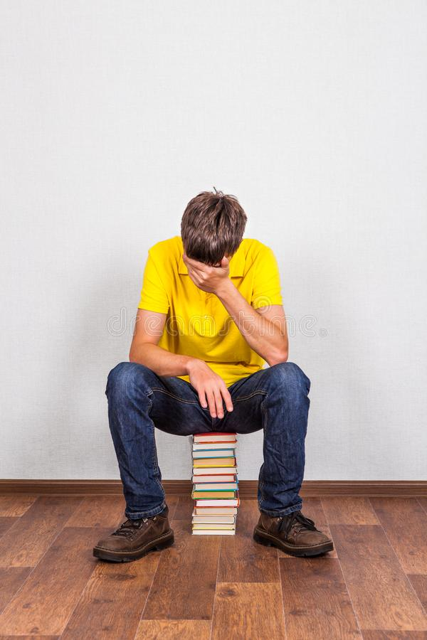 Ledsen ung man med böcker royaltyfri foto