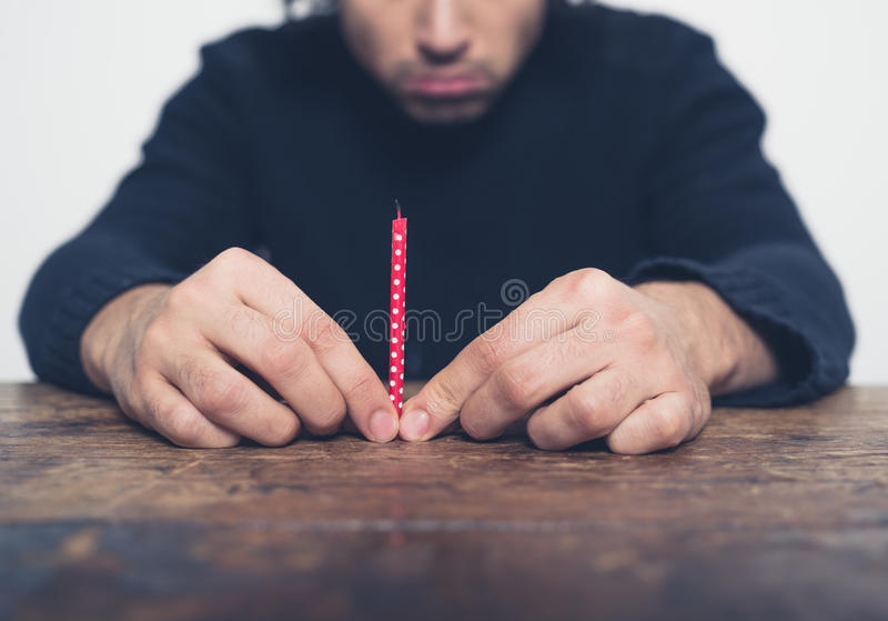 Ledsen ung man med den lilla stearinljuset fotografering för bildbyråer