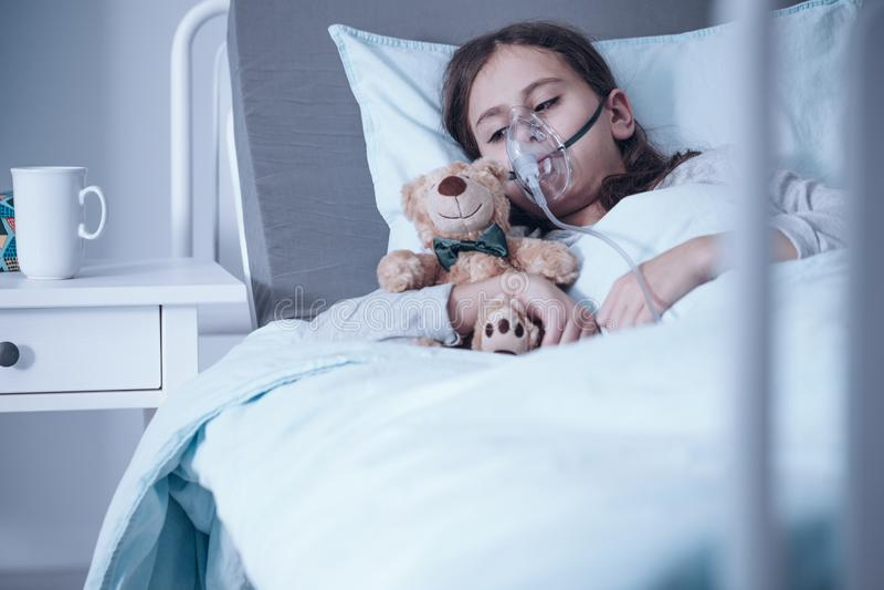 Ledsen unge med cystic fibrosis som ligger i en sjukhussäng med syremaskeringen och den flotta leksaken royaltyfria foton