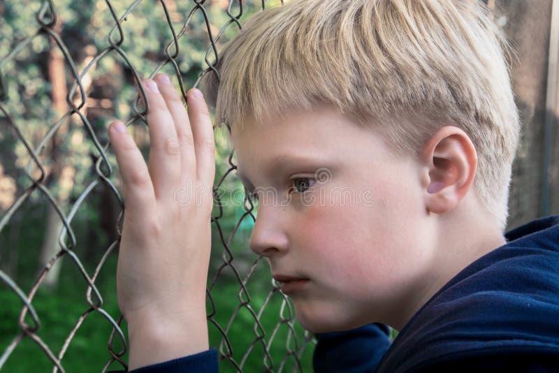 Ledsen uppriven pojke arkivfoto