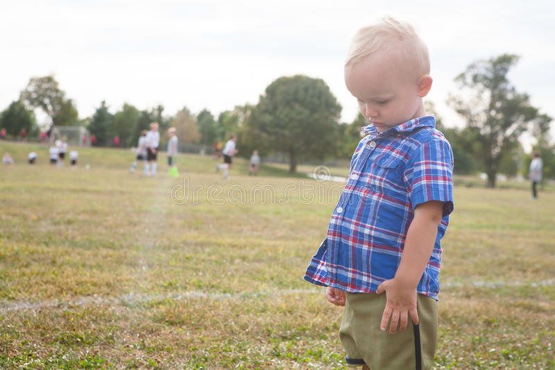 Ledset barn vid fotbollfältet royaltyfri fotografi