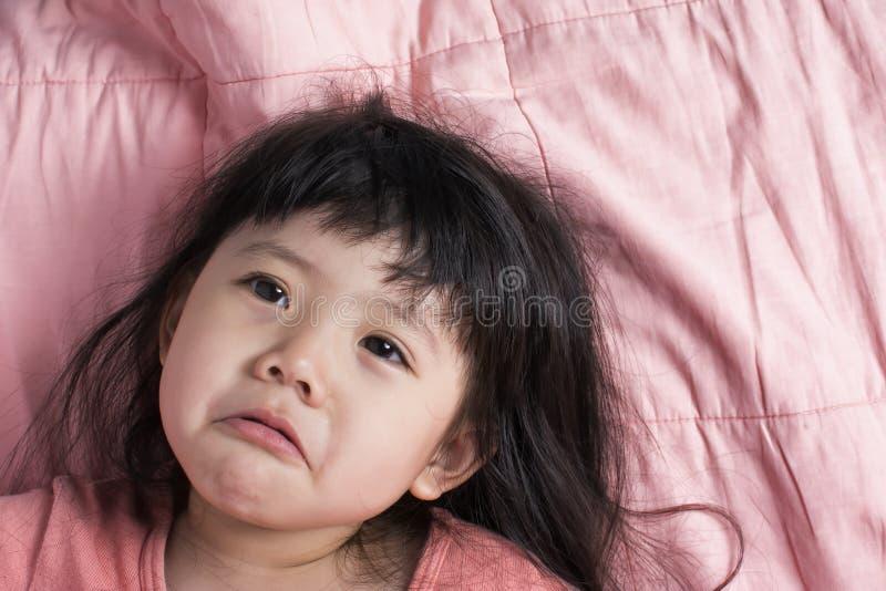 Ledset behandla som ett barn den Asien flickan på soffan i rosa färger arkivbild