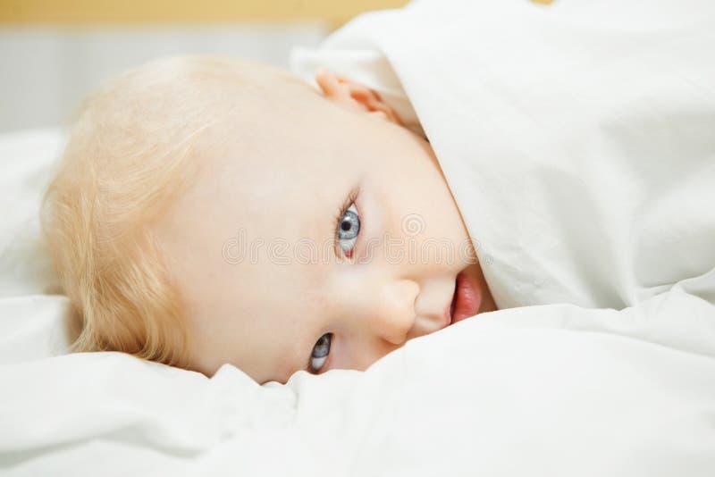 Ledset behandla som ett barn med förkylning som lögner täckte med förbigått royaltyfri foto