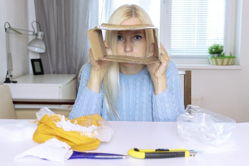 Ledset blont kvinnasammanträde vid tabellen, når unboxing av en jordlott och det har sett till och med den tomma asken, alla obje royaltyfria foton