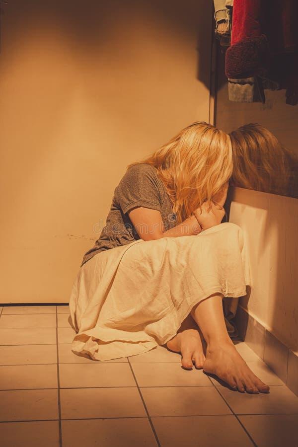Ledset, deprimerat och ensamt kvinnasammanträde på tegelplattor för ett golv, i en kjol, barfota arkivfoto