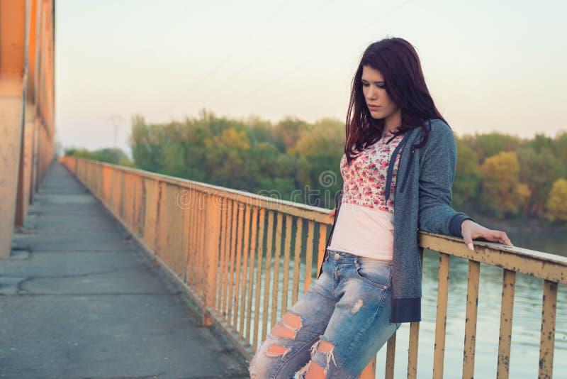 Ledset ensamt anseende för tonårs- flicka på bron på härlig spri arkivfoton