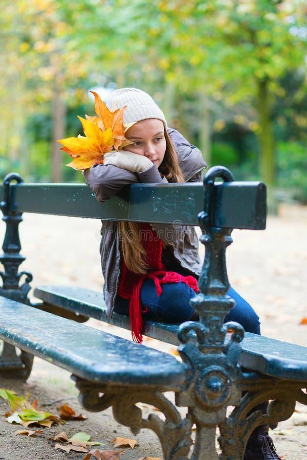 Ledset flickasammanträde på en bänk parkerar in royaltyfria bilder