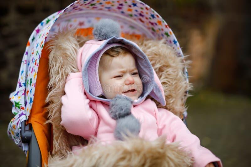 Ledset gråta litet härligt behandla som ett barn flickan som sitter i pramen eller sittvagnen på höstdag Olyckligt trött och utma fotografering för bildbyråer