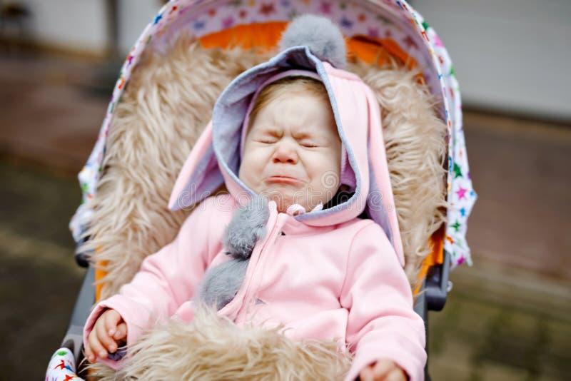 Ledset gråta litet härligt behandla som ett barn flickan som sitter i pramen eller sittvagnen på höstdag Olyckligt trött och utma arkivbilder