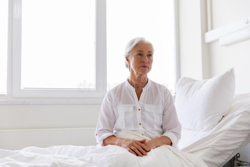 Ledset högt kvinnasammanträde på säng på sjukhussalen royaltyfri foto
