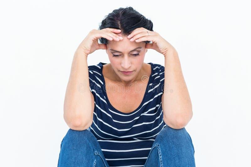 Ledset kvinnasammanträde med huvudet i händer arkivfoto