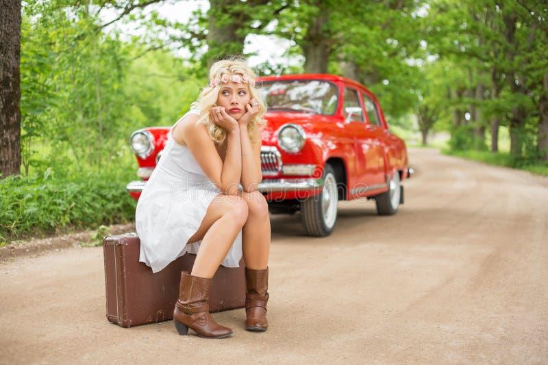Ledset kvinnasammanträde på resväskan arkivfoton