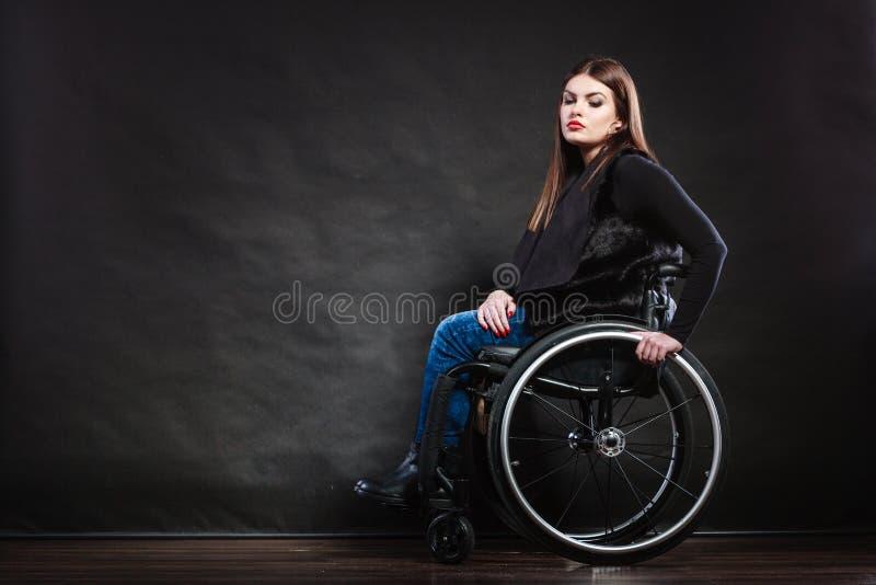 Ledset kvinnasammanträde på rullstolen arkivbild