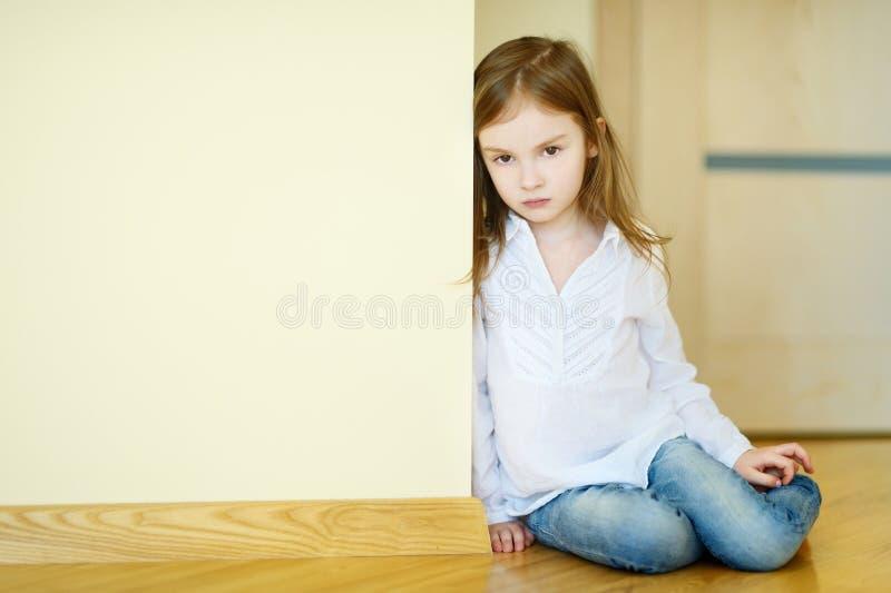 Ledset liten flickasammanträde på ett golv royaltyfria bilder